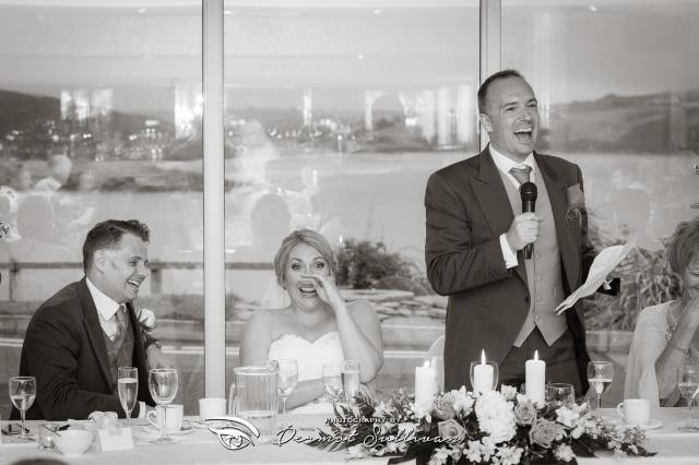 Marc delivering a wedding speech holding a microphone and sheet of paper