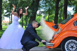 Wedding car with smoke fumes and a stressed bride next to a man in a suit