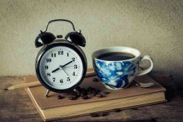 An alarm clock next to black coffee in a china cup representing an urgent Best Man speech