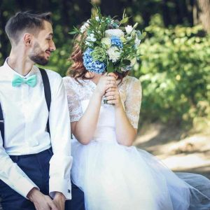 BrideGroom sitting next to bride who is hiding her face behind flowers