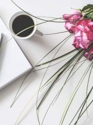 A close up of white writing paper next to a cup of black coffee and a bouquet of wedding flowers