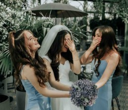 Bride holding flowers with bridesmaid and Maid of Honour either side of her. All of them are laughing